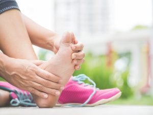 Closeup woman massaging her painful foot while exercising. Running sport injury concept.